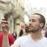 człowiek zrobić zdjęcie z telefonu komórkowego na ulicy — Zdjęcie stockowe