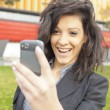 Royalty-Free Stock Photo: Young Woman with funny hair smile using cell phone walking
