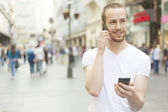 Men speaking on one mobile phone and holding secund cell in hand — Stock Photo