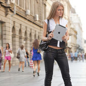 Woman with ipad tablet computer waiting on urban street — Stock Photo