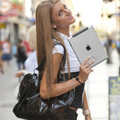 Woman with iPad tablet computer walking on urban street — Stock Photo