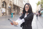 Businesswoman on street with tablet computer — Stock Photo