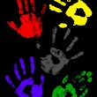 Colorful handprints on a black background — Stock Photo