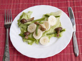 Creative salad from fried fungi and stalks of garlic and sweet bananas — Stock Photo