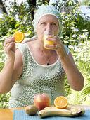 The happy adult woman drinks fresh orange juice — Stock Photo