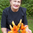 Royalty-Free Stock Photo: The happy smiling woman and orange flowers of a lily in a garden