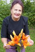 Lily bir bahçe mutlu gülümseyen kadın ve portakal çiçekleri — Stok fotoğraf