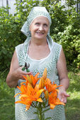 The happy woman grows up decorative lilies — Stock Photo