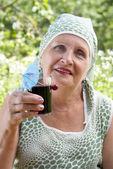 Woman drinks fresh cherry juice — Stock Photo