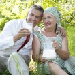 Happy femaly drinks pair milk in a summer gard — Stock Photo