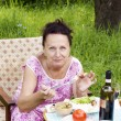 Stock Photo: The adult woman has dinner in a summer green garden