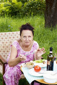 The adult woman has dinner in a summer green garden — Stock Photo
