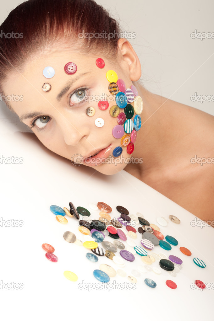 Beautiful young woman with colourful buttons on her face  Stock Photo #11096808