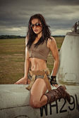 Sexy woman astride aircraft fuselage — Stock Photo