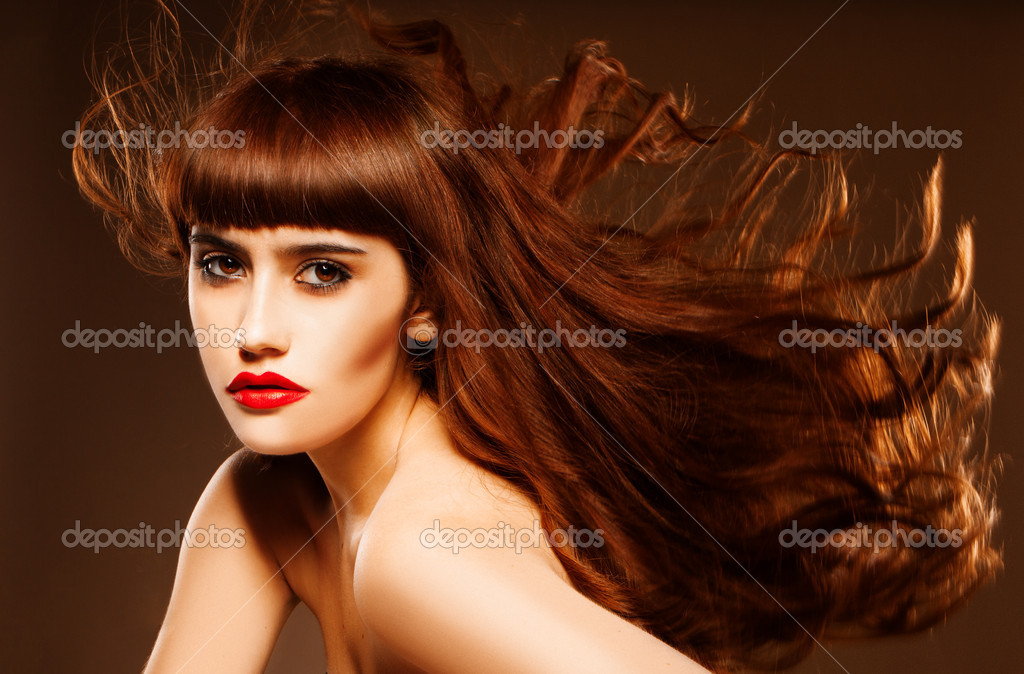 Sultry beautiful redhead with overemphasised red lips and her long hair flying in the breeze — Stock Photo #11535107