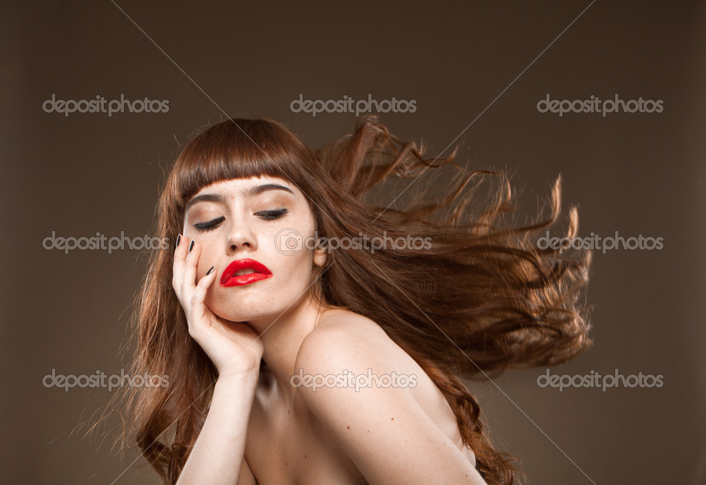 Sassy brunette with red lips and her hair flying to the side against a dark brown studio background — Stock Photo #11535109