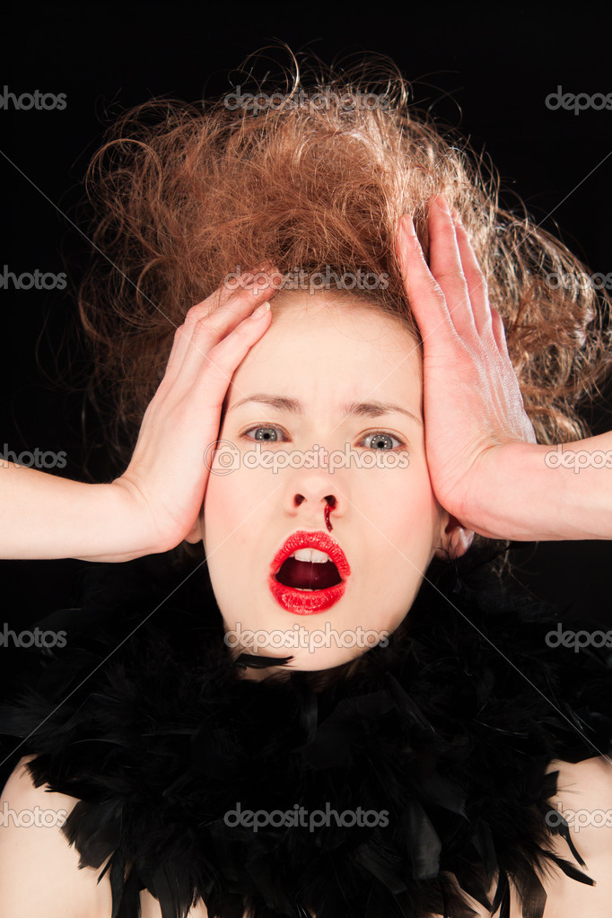 Beautiful young woman raising her hands to her head in horror as she bleeds from her nose  Stock Photo #11540215