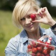 Beautiful blonde woman picking strawberries — Foto Stock