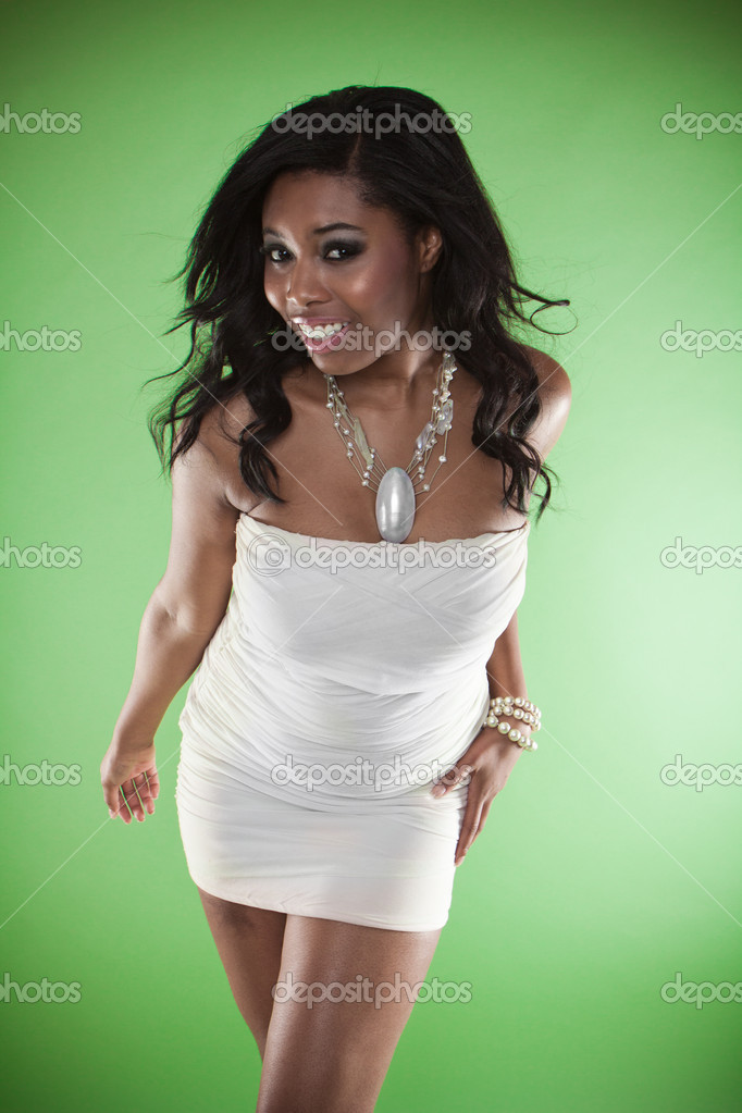 Sexy smiling African woman in a strapless cocktail dress leaning towards the camera provocatively flaunting her large breasts — Photo #11552822