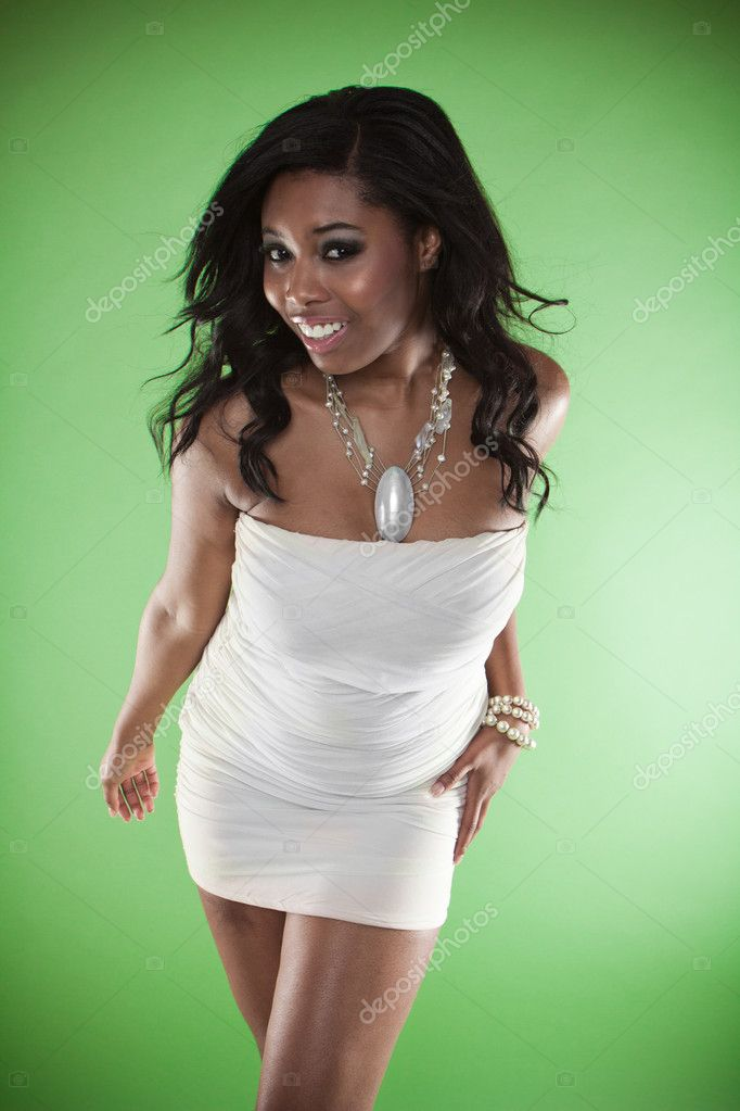 Sexy smiling African woman in a strapless cocktail dress leaning towards the camera provocatively flaunting her large breasts — Stockfoto #11552822