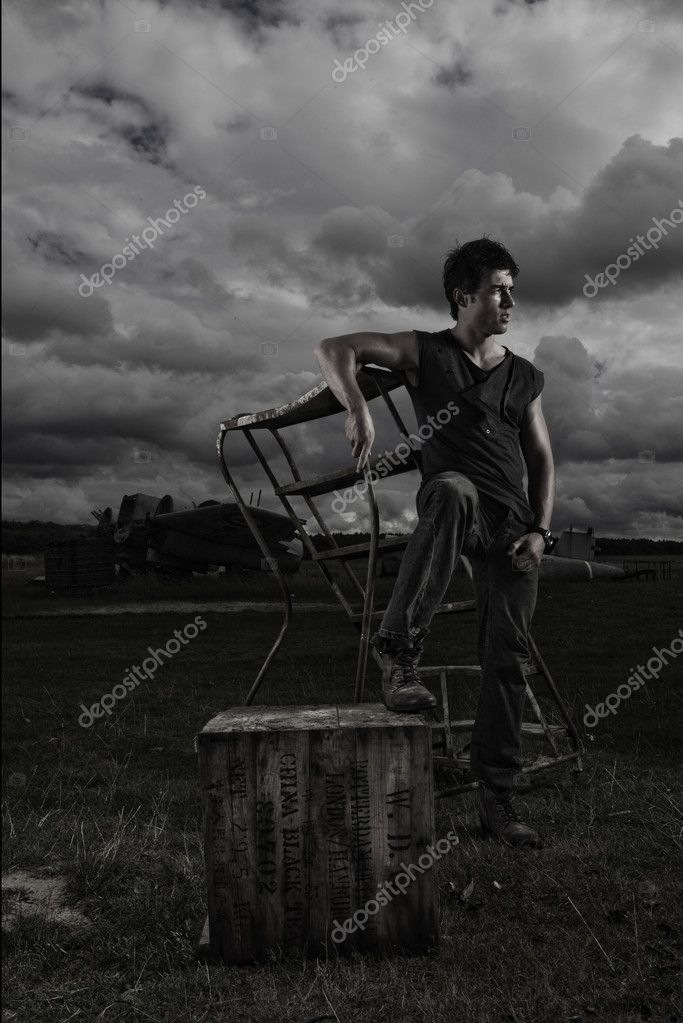 Dark stormy portrait of a casual sexy man posing on portable steps alongside an old crate outdoors under a threatening sky — Stock Photo #11653986