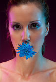 Beautiful woman with flower in mouth — Stock Photo
