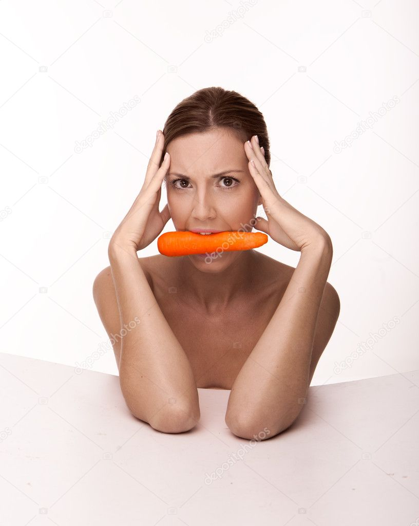 Head and shoulders portrait of a sexy brunette with a carrot gripped between her teeth on a white studio background — Stock Photo #11748204