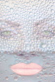 Cara de chica guapa con ojos verdes contra gotas de agua transparente — Foto de Stock