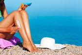 Tan kadının bacaklarının üzerinde güneş koruyucu uygulanıyor — Stok fotoğraf
