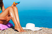 Tan woman applying sunscreen on her legs — Foto Stock