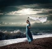 Blond kvinna i lång klänning på stormigt hav — Stockfoto