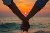 Pareja tomados de las manos en el mar al atardecer — Foto de Stock