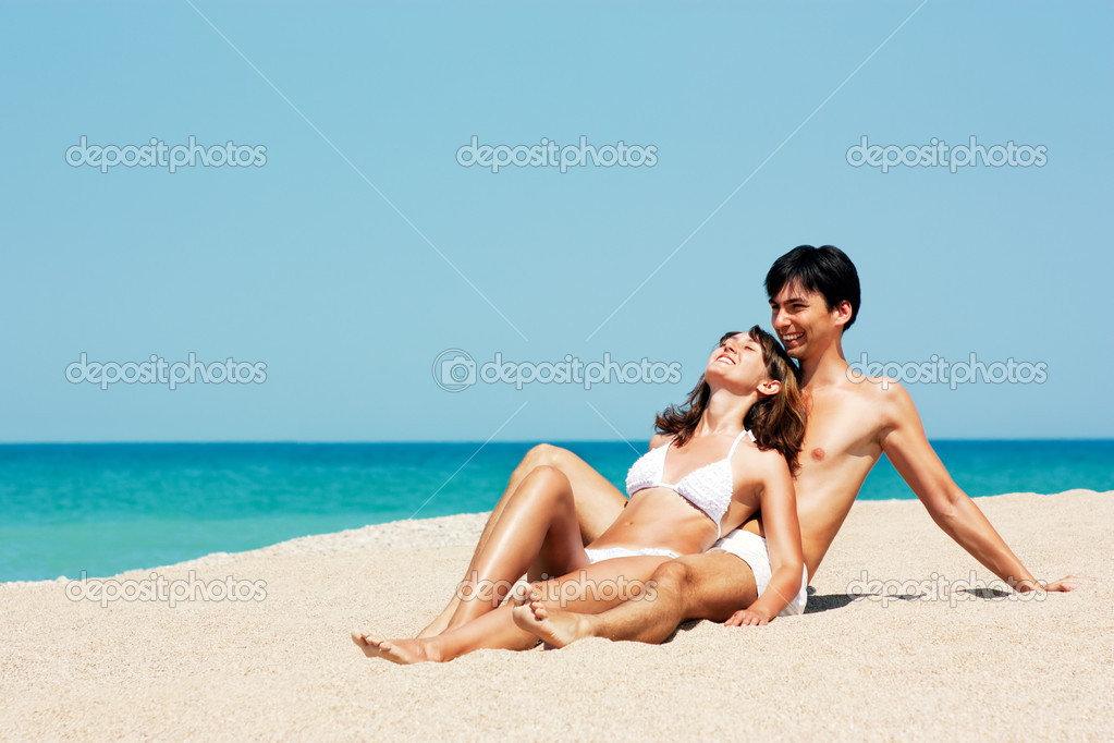 Happy Young Couple Lying on a Beach and Holding Each Other — Stock Photo #12141114