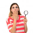 Woman through a magnifying glass with a surprised — Stock Photo