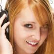 Stock Photo: Young redhead womlistening to music