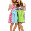 Two happy bavarian dressed girls showing thumbs up — Stock Photo