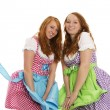 Two bavarian dressed girls fighting with wind — Stock Photo
