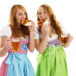 Two bavarian dressed women eating pretzels — Stock Photo
