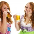 Two bavarian girls laughing and drinking beer — Stock Photo