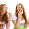 Two bavarian women eating pretzels and holding beer — Stock Photo