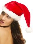 Beautiful brunette woman wearing santas hat looking over her shoulder — Stock Photo
