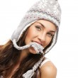 Young brunette woman holding part of her winter cap with her mouth — Stock Photo #10775564