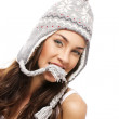 Young brunette woman holding part of her winter cap with her mouth — Stock Photo