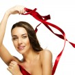 Gorgeous woman playing with a red ribbon - Stock Photo