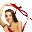 Stock Photo: Gorgeous womplaying with red ribbon