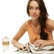 Upset young woman with newspaper and latte macchiato at a table — Stock Photo
