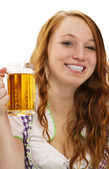 Young woman in bavarian dress showing a glass with beer — Stock Photo