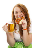 Redhead woman in bavarian dress with beer eating pretzel — Stock Photo