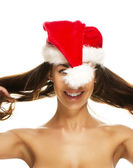 Young brunette woman having fun with santas hat — Stock Photo