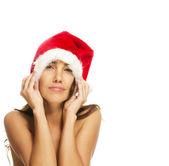Ung kvinna som bär santas hat att göra ansikten — Stockfoto